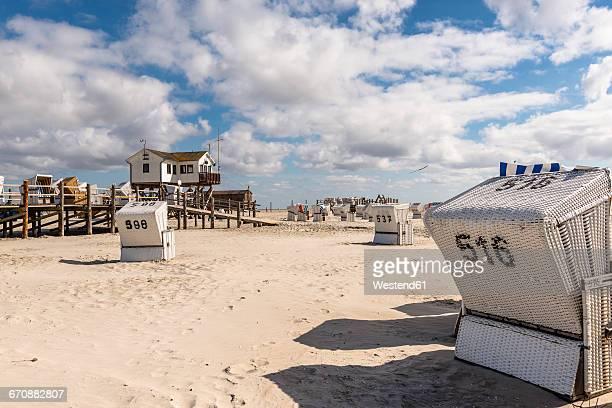 germany, schleswig-holstein, st peter-ording, stilt house and hooded beach chairs at beach - sankt peter ording stock-fotos und bilder