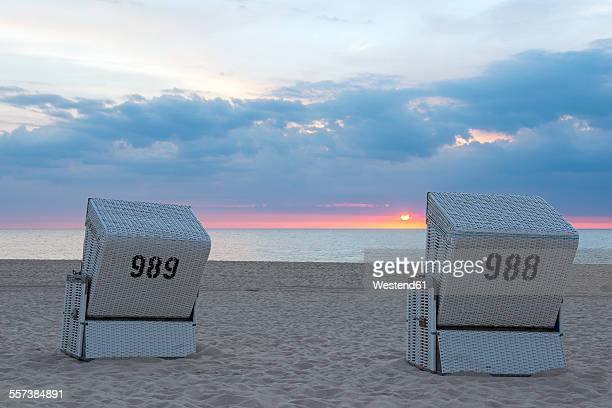 Germany, Schleswig-Holstein, Sylt, Westerland, hooded beach chairs on beach at sunset