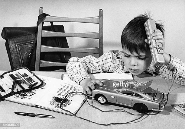 school boy playing with a wire controlled toy car about 1965