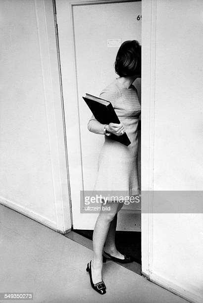 Germany secretary woman looking through door in the office personal assistant