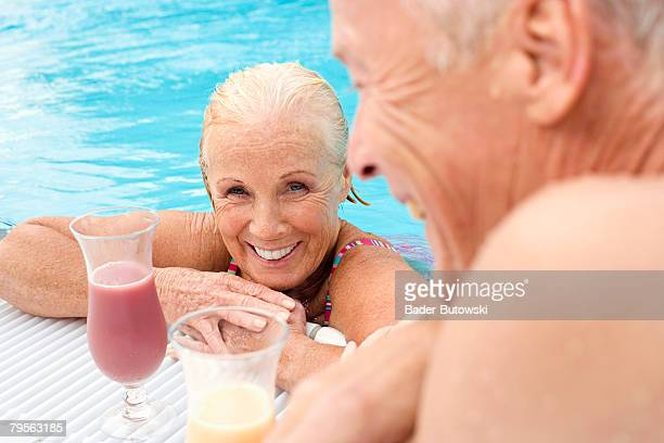 Germany, senior couple with cocktail at swimming pool, smiling