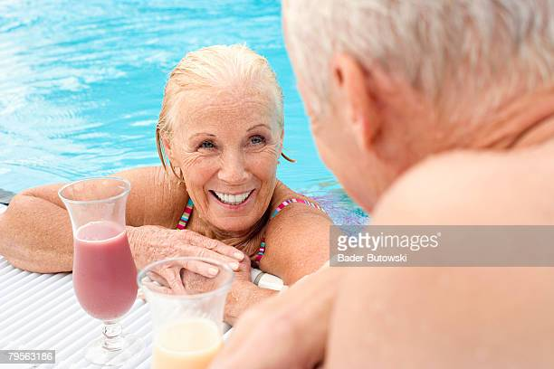 'Germany, senior couple drinking cocktail at pool'