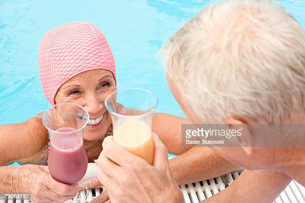Germany, senior couple holding cocktail at swimming pool, elevated view
