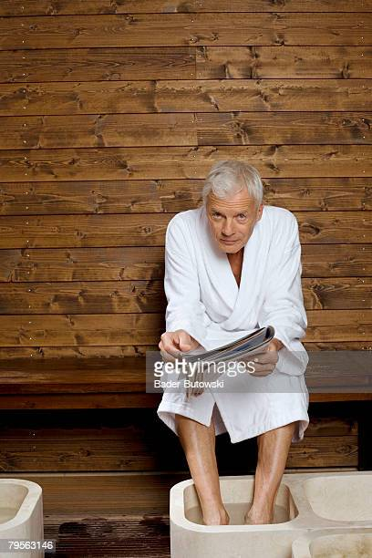 Germany, senior man with feet in washtub holding magazine, portrait