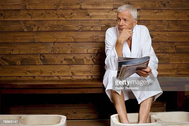 Germany, senior man with feet in washtub holding magazine