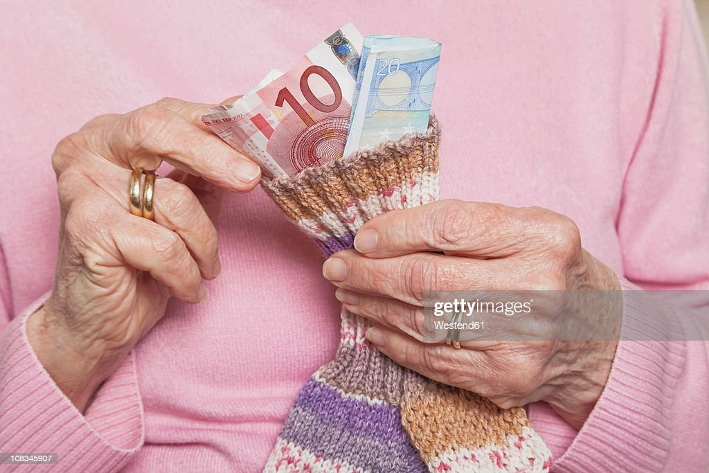Germany, Senior woman counting money from money sock, mid section : Stock-Foto