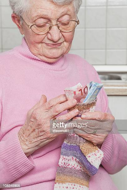 Germany, Senior woman counting money from money sock, smiling