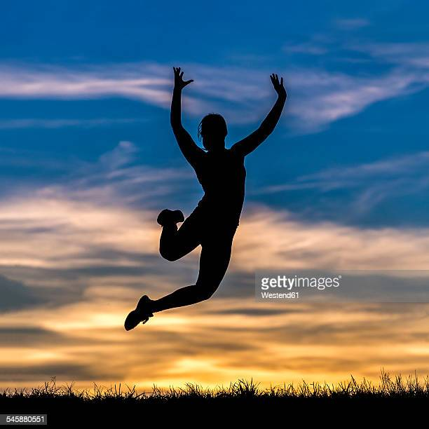 Germany, Silhouette of a woman jumping at sunset