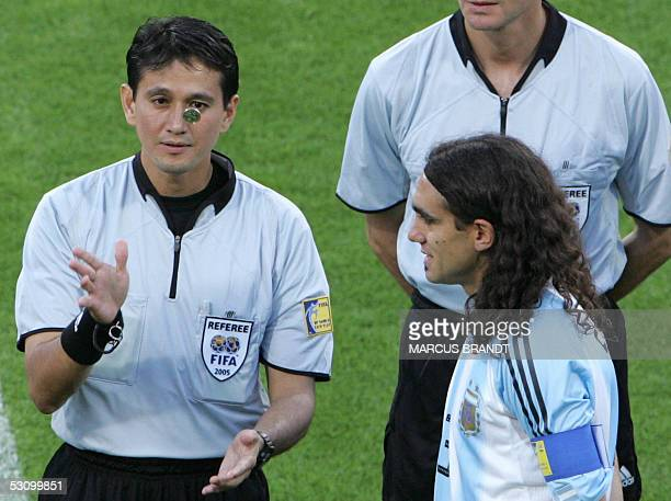 Singapore referee Shamsul Maidin throws a coin as Argentine defender and captain Juan Pablo Sorin looks on at the begining of the 2005 FIFA football...