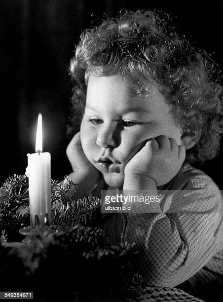 Germany small child admiring an advent wreath in the fifties