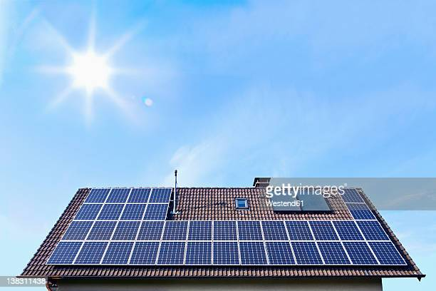 Germany, Solar panels on houseroof in front of blue sky with sun