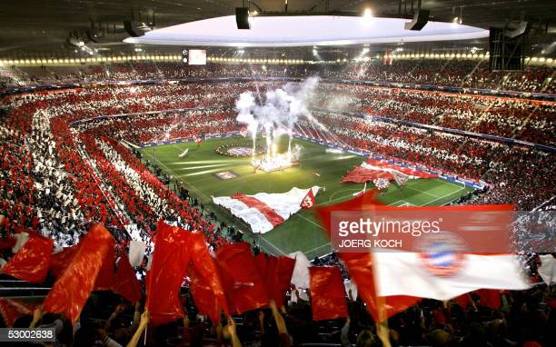 Spectators wave red and white flags, the colours of Bayern Munich, during the inauguration of the new Allianz Arena Football stadium 31 May 2005 in...