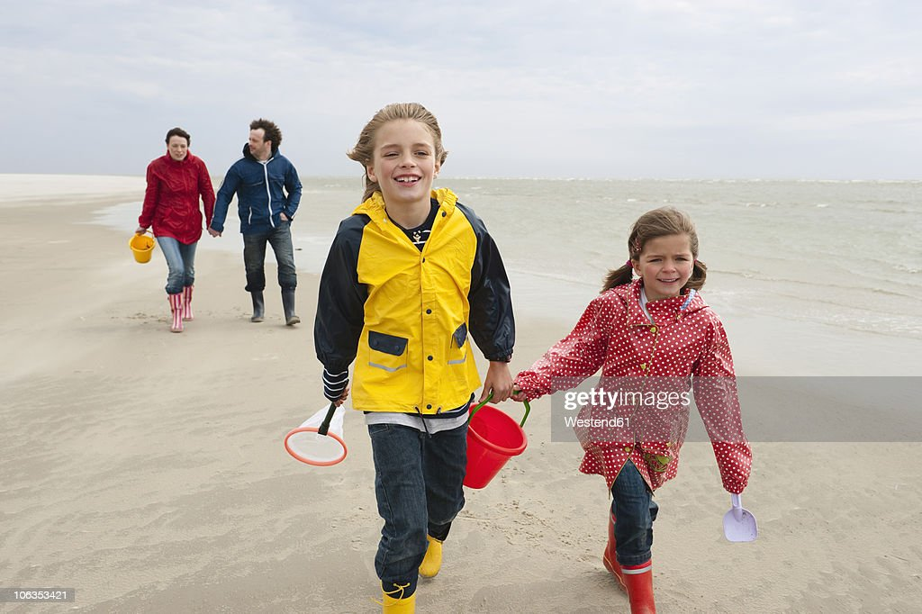 Germany, St. Peter-Ording, North Sea, Children (6-9) with parents walking on beach : Stock Photo