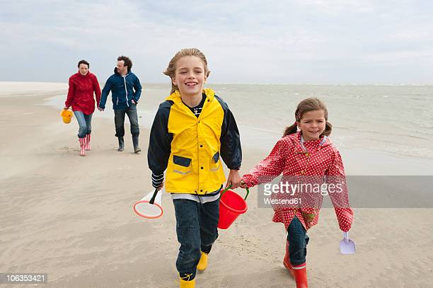 germany, st. peter-ording, north sea, children (6-9) with parents walking on beach - schleswig holstein stock pictures, royalty-free photos & images