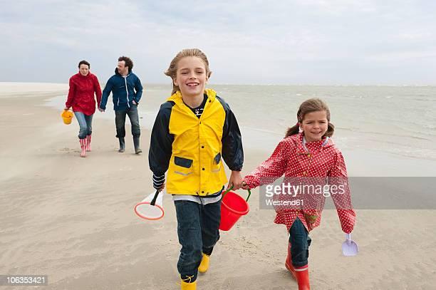 germany, st. peter-ording, north sea, children (6-9) with parents walking on beach - schleswig holstein stock-fotos und bilder