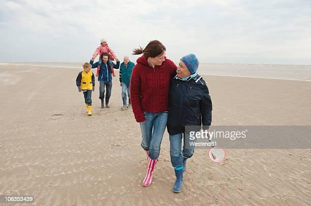 germany, st. peter-ording, north sea, family walking on beach - mittelgroße personengruppe stock-fotos und bilder