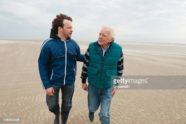 Germany, St. Peter-Ording, North Sea, Senior man and son walking on beach