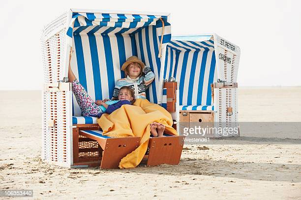 germany, st.peter-ording, north sea, children (6-9) resting on hooded beach chair - german north sea region stock pictures, royalty-free photos & images