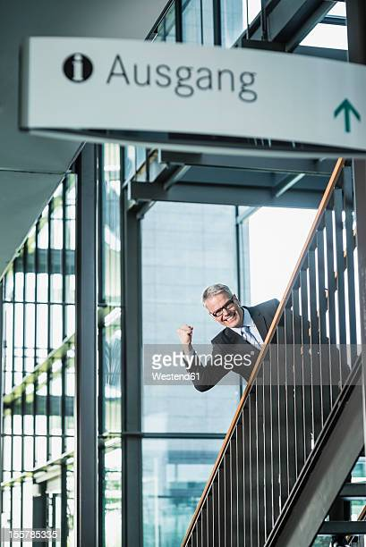 Germany, Stuttgart, Businessman moving up on office staircase, portrait, smiling
