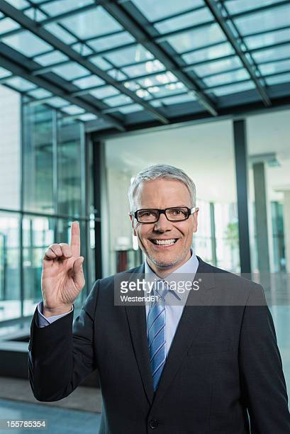 Germany, Stuttgart, Businessman with one finger, smiling, portrait