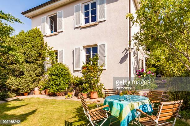 Germany, Stuttgart, one-family house, garden table with lawn chairs