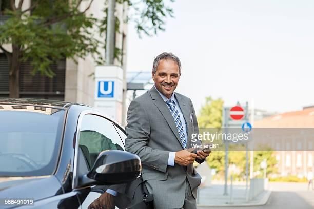 Germany, Stuttgart, portrait of smiling businessman leaning on car