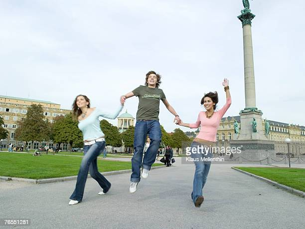 Germany, Stuttgart, teenage boy and girls (16-17) jumping in front of building