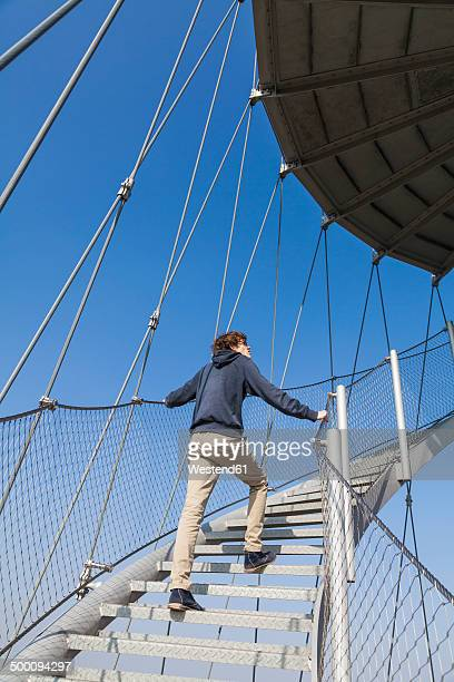 Germany, Stuttgart, Teenage boy climbing stairs of Killesberg Tower