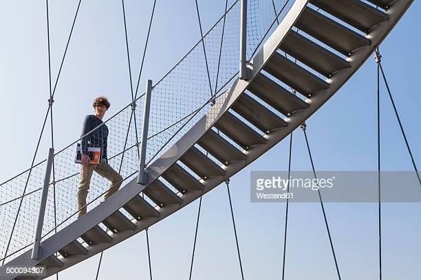 Germany, Stuttgart, Teenage boy climbing stairs of Killesberg Tower