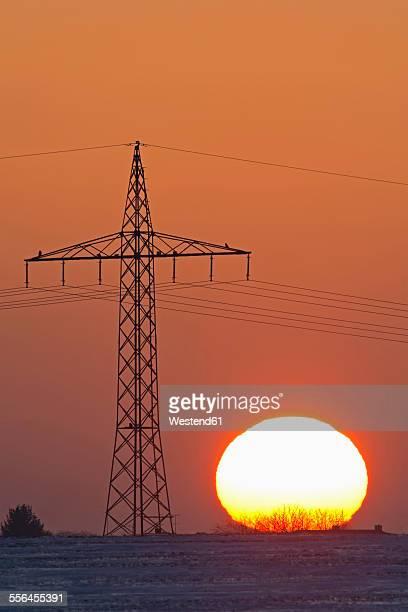 Germany, sunset besides electricity pylon