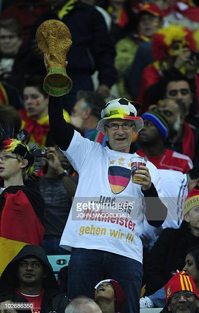 A Germany supporter holding up a mock World Cup trophy wears a shirt reading ' and now we are going to be World Champions' prior to the 2010 World...