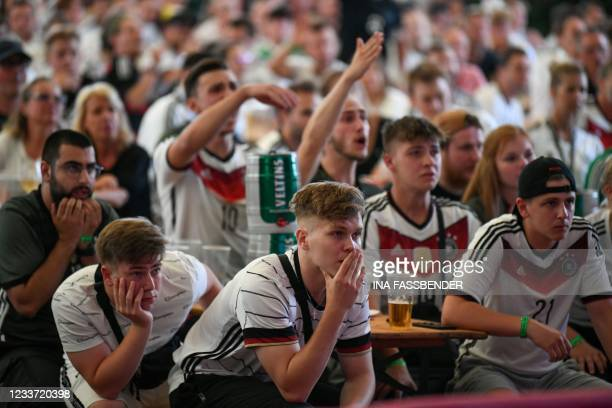 Germany supporters react after England scored their second goal during the UEFA EURO 2020 round of 16 football match between England and Germany at...