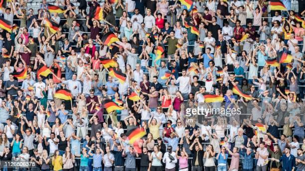 deutschland-fans schwenkten ihre fahnen auf einem stadion - deutsche kultur stock-fotos und bilder