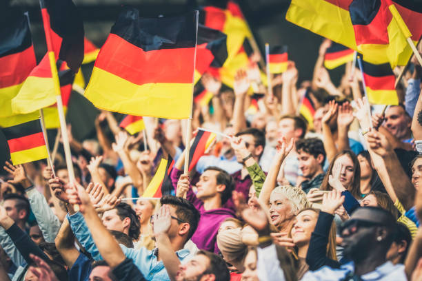 germany supporters waving their flags on a stadium - germany stock pictures, royalty-free photos & images