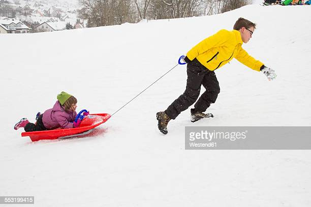 Germany, Swabian mountains, brother pulling his little sister lying on sledge