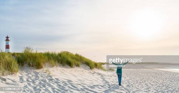 germany, sylt, north sea, happy woman strolling on sandy beach - north sea stock pictures, royalty-free photos & images