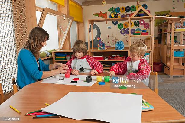 Germany, teacher helping two boys (3-7) finger painting in nursery