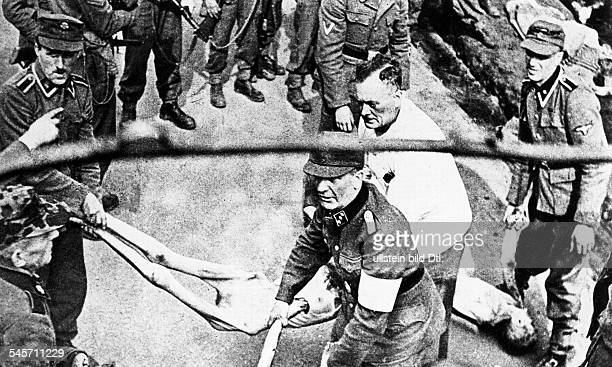 Germany Third Reich concentration camps 193945 Former SS personel transporting the dead bodies of inmates to a mass grave after the liberation of...