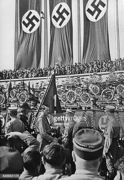 Germany Third Reich Nuremberg Rally 1934 Adolf Hitler hallowing new standards with the socalled 'blood flag' during a roll call of the SA and SS