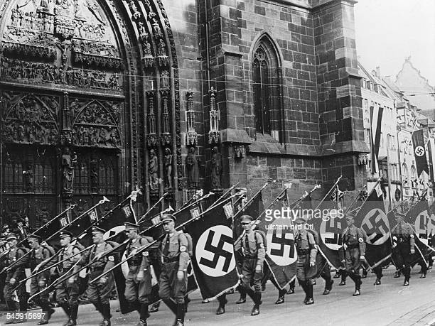 Germany Third Reich Nuremberg Rally 1934 The political leaders of the Nazi party marching through Nuremberg with the flags of the party organisations...