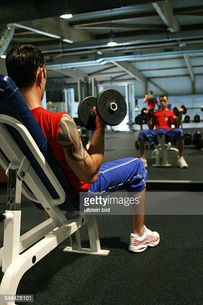 DEU Germany Thomas with the red shirt is 25 years old He has first signs of a breast with little lumps under his nipples Here in a fitness centre
