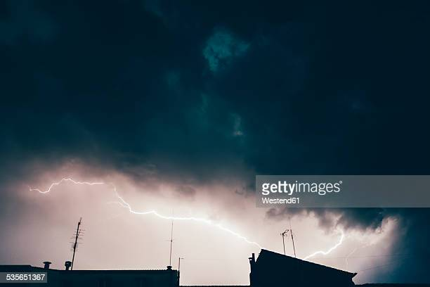 Germany, thunderstorm and lightning over rooftops