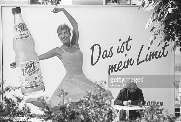 Germany Thuringia Jena lonely man drinking beer in front of a big poster for the limonade 'Limit'