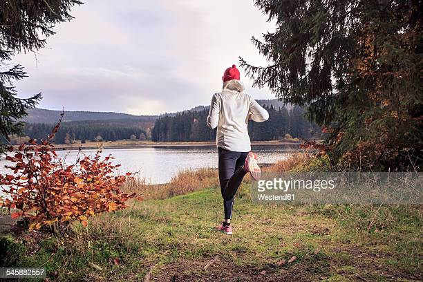 germany, thuringia, woman running through the forest by the lake near alsbach - thuringia stock pictures, royalty-free photos & images