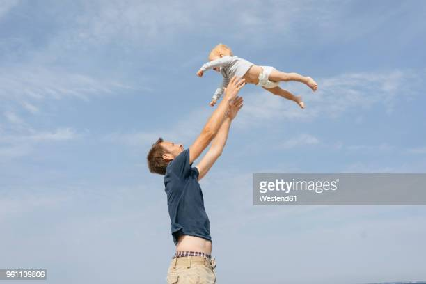 Germany, Timmendorfer Strand, Father throwing son in the air