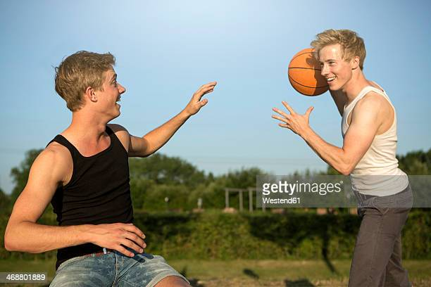 germany, two young man meeting up to play basketball - oberhausen stock-fotos und bilder