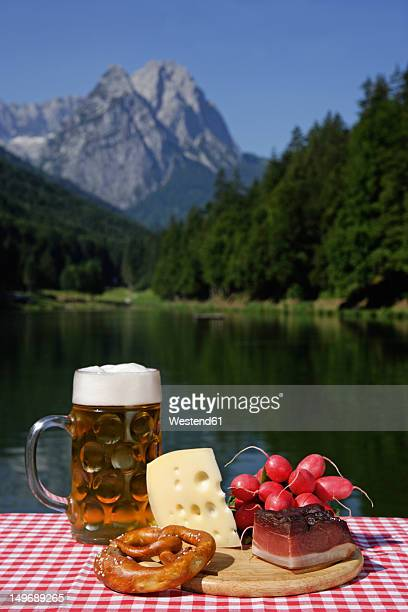 Germany, Upper Bavaria, Bavarian snacks on table, mountain with lake in background