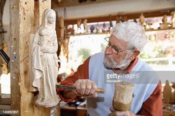 Germany, Upper Bavaria, Craftsperson carving statue