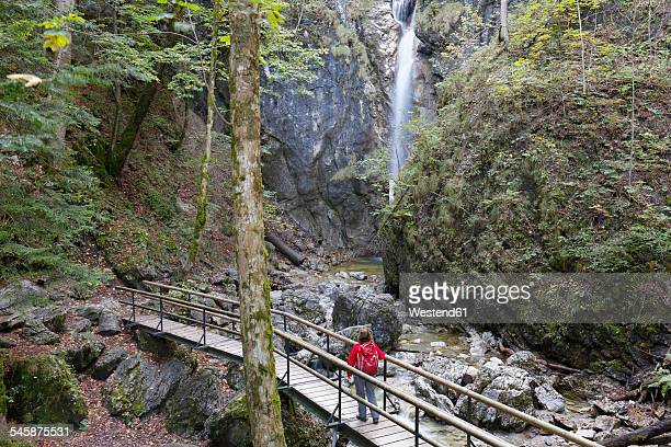 germany, upper bavaria, kochel am see, lainbach fall, hiker standing on bridge - oberbayern stock-fotos und bilder