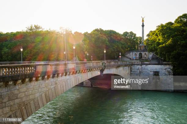 germany, upper bavaria, munich, luitpoldbrucke crossing isar river with angel of peace in background - fiume isar foto e immagini stock